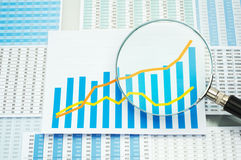 Many charts, graph and magnifying glass. Stock Photos
