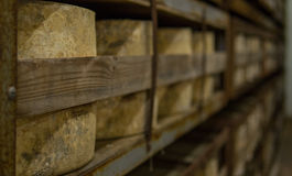 Many cheese wheels being stored in a Cheese Cathedral Stock Photo