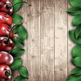 Many cherries and leaves on wooden background. Stock Photos