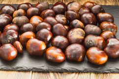 Many chestnut fruits are located on a wooden table view from the side.  royalty free stock photos
