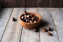Many chestnuts in a wooden bowl and some scattered on the table royalty free stock photography