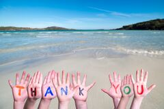 Many Children Hands Building Word Thank You, Ocean Background