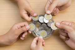 Many children holding coins putting in glass. concept saving mon stock photo