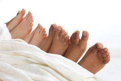Many children`s feet peeking from under the blanket. The many children`s feet peeking from under the blanket royalty free stock images