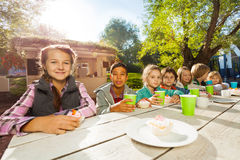 Many children sit at table with bright cups Stock Photo