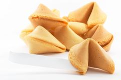 Many Chinese fortune cookies stacked up. One stand out, on white background, side view, with a white piece of paper for entering text/fortune Stock Image