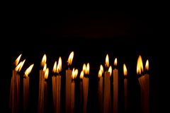 Many christmas candles burning at night on the black background stock photo