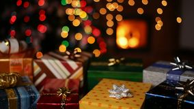Many christmas gifts in front of fireplace and blurry lights on xmas tree stock footage