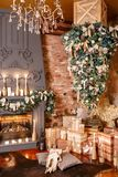 Many Christmas gifts. Winter home decor. Christmas in loft interior against brick wall. Stock Photos