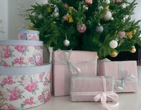 Many Christmas presents on the floor on a Christmas tree background. Delicate colors of materials and Christmas decorations stock photography
