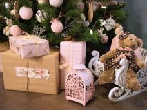 Many Christmas presents on the floor on a Christmas tree background. Delicate colors of materials and Christmas decorations stock photos