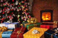 Many christmas presents in front of xmas tree and fireplace Stock Photography