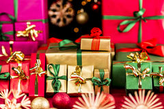 Many Christmas Presents Grouped by Color. Plenty of gifts prepared for the handing out of Christmas presents. Piles grouped in green, gold, and red. Shallow Royalty Free Stock Photography