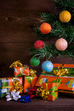 Many Christmas presents under the tree and decorations. On plank background stock image