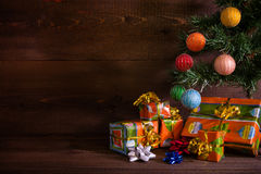 Many Christmas presents under the tree on plank background Stock Photos