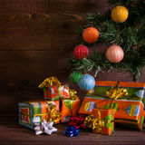 Many Christmas presents under the tree. On plank background stock photography