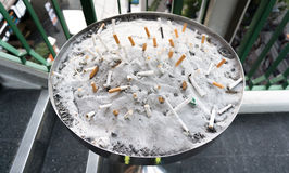 Many Cigarette butts in the sand on an ashtray. Many Cigarette butts in the sand on a big ashtray Stock Images