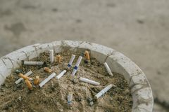 Many cigarette stub in sand ashtray. The rest of cigarettes in the ashtray. There are many types of cigarette stub on the sand in. The ashtray. A cigarette is stock image