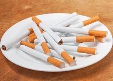 Many cigarettes on the plate Royalty Free Stock Images