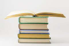 Many closed books lying on a white background. One open book. Horizontal stock image