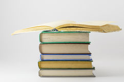 Many closed books lying on a white background.One open book. Royalty Free Stock Photo