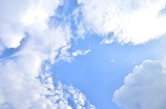 Many clouds in the bright blue sky. Stock Image