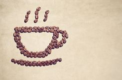 Coffee cup symbol made out of coffee beans. Many coffee beans forming a coffee cup symbol on a brownish background. Copy space the right Royalty Free Stock Photos