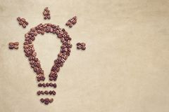 Light bulb symbol made out of coffee beans with copy space. Many coffee beans forming a glowing light bulb symbol on a brownish background. New idea concept Royalty Free Stock Photo
