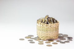 Many coin in a bamboo basket. Many coin in a bamboo basket on white background. Concept financial or business. Keep saving money for good thing in the future royalty free stock images