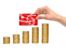 Many coins in column and hand with credit card. Isolated on white royalty free stock photo