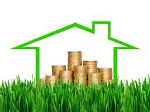 Many coins in column in house over green grass. Financial concep Stock Photos