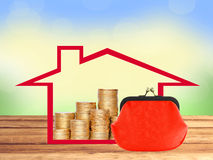 Many coins in column in house and red purse on wooden table Royalty Free Stock Image