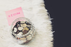 Many coins in a money jar with wedding label on jar Royalty Free Stock Photography