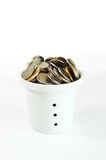 Many coins in the pot on white. A full bucket of coins on white background Royalty Free Stock Images