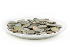 Many coins on white dish on white background Stock Photo