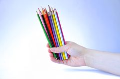 Many color pencils in hand on white background royalty free stock photography