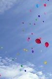 Many colored balloons fly in the blue sky with clouds Stock Image