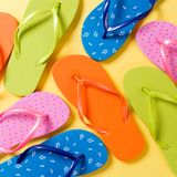 Many colored flip flops on yellow background. Copy space top view.  royalty free stock photos