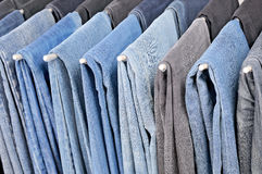 Many colored jeans hanging on hangers Royalty Free Stock Images