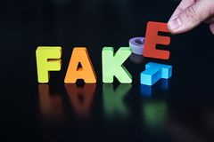 Many-colored letters forming word FAKE instead of FACT on black background. Person sets letters F, A, K on black surface pushing stock images