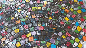 Many colored painted cobble stone pavement in a rainy day Stock Photos