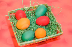 Many colored painted easter eggs in a basket with green grass Stock Photos