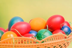 Many colored painted easter eggs in a basket with green grass Royalty Free Stock Image