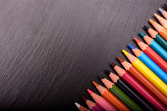 Many colored pencils on a black stone slate, place for text Stock Image