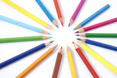 Many colored pencils in circle in a white background. Composition Stock Photo