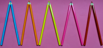 Many colored pencils on a pink background stock photos