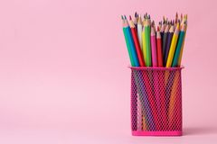 many colored pencils in a pink glass on a bright trendy pink background. space for text royalty free stock photos