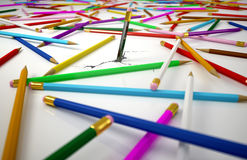 Many colored pensils, spread on white surface. Royalty Free Stock Image