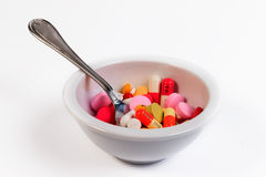 Many colored pills and capsules in a bowl with a spoon. Stock Images