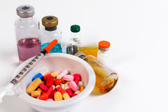Many colored pills, capsules and syringe in a cup with a spoon and bottle of vaccine. Royalty Free Stock Photos